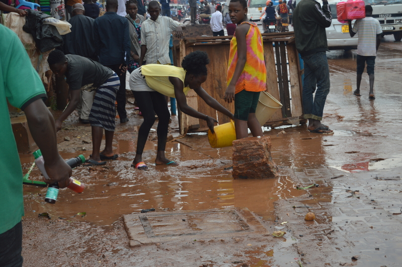 Bwaise residents cleaning up after a downpour. Photo Credit; TAU.JPG